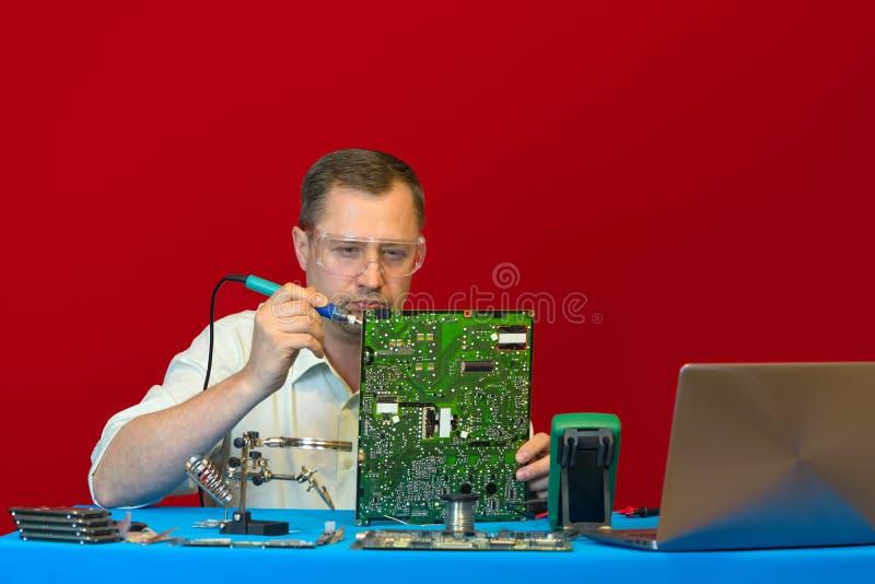 Радиотехническая схема человека паяя Пункт обслуживания инженера ремонтирует ЖК-ТЕЛЕВИЗОР электропитания стоковое изображение