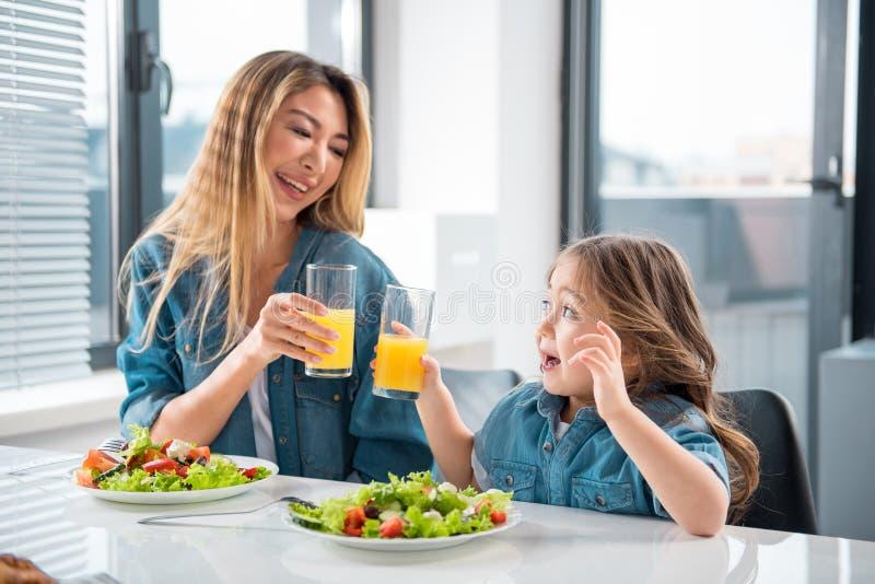 Радостная азиатские женщина и девушка выпивая апельсиновый сок стоковое фото rf