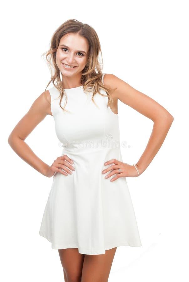 Радостная девушка в белом платье на белой предпосылке стоковая фотография
