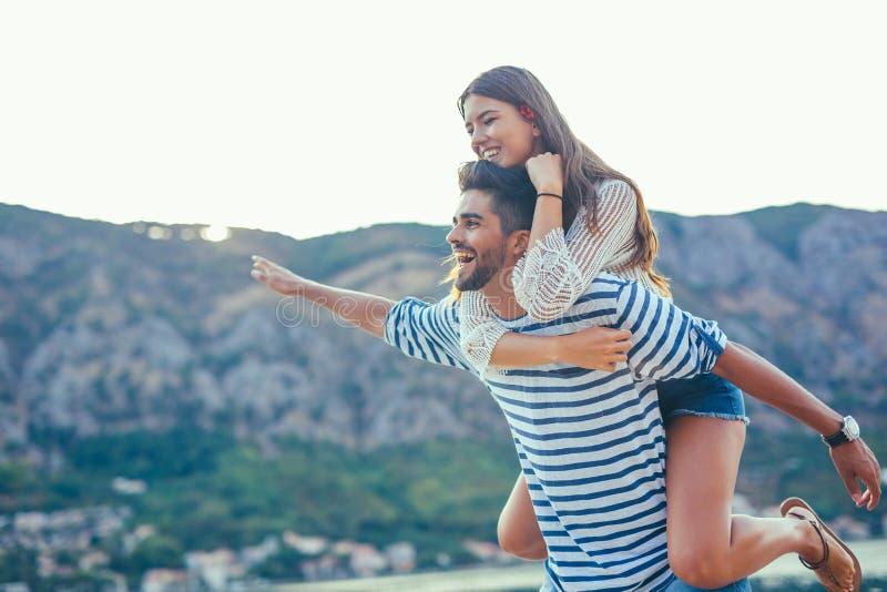 Радостная девушка перевозить на молодом парне стоковые фотографии rf