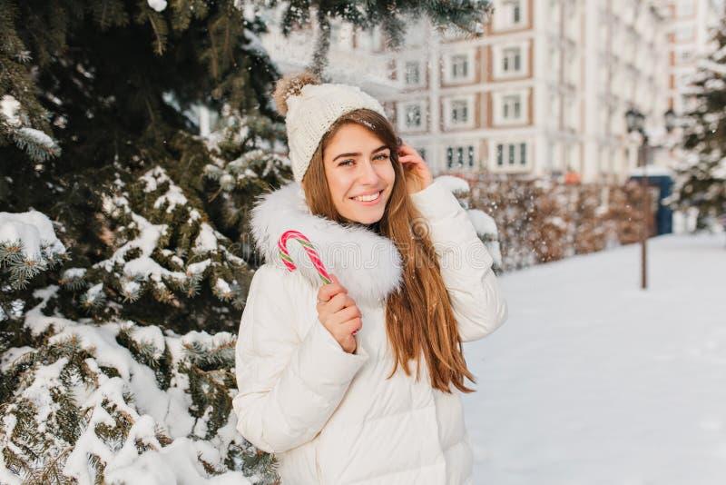 Радостная европейская женщина в теплых одеждах наслаждаясь помадками на снежной улице Фото Oudoor довольной длинн-с волосами дамы стоковое фото rf
