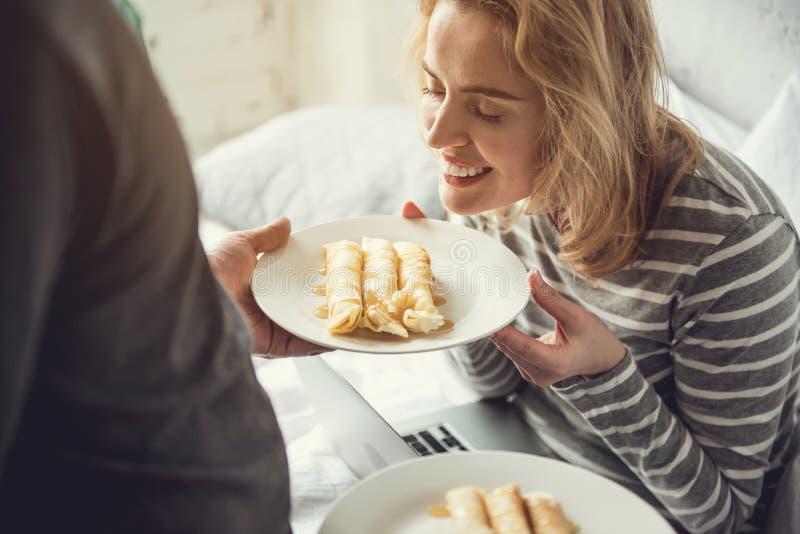 Радостная женщина принимает вкусный завтрак от парня стоковые фото