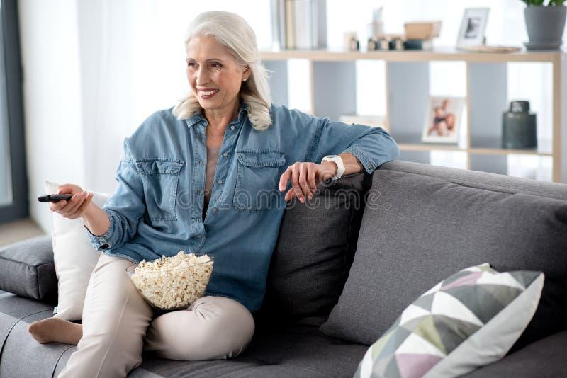 Радостная зрелая дама развлекая с телевидением в живущей комнате стоковая фотография