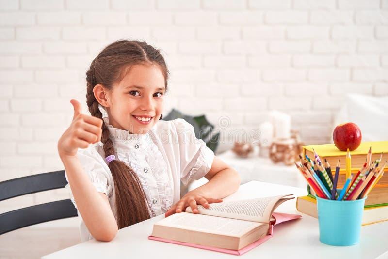 Радостная маленькая девочка сидя на таблице с карандашами и учебниками Счастливый зрачок ребенка делая домашнюю работу на таблице стоковая фотография rf