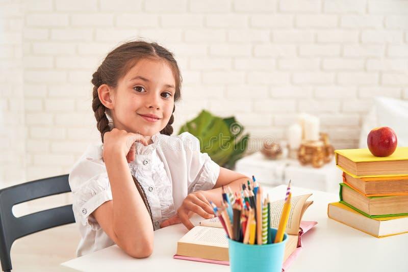 Радостная маленькая девочка сидя на таблице с карандашами и учебниками Счастливый зрачок ребенка делая домашнюю работу на таблице стоковые фото