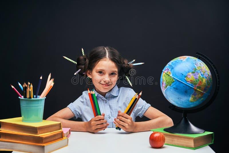 Радостная маленькая девочка сидя на таблице с карандашами и учебниками Счастливый зрачок ребенка делая домашнюю работу на таблице стоковое фото
