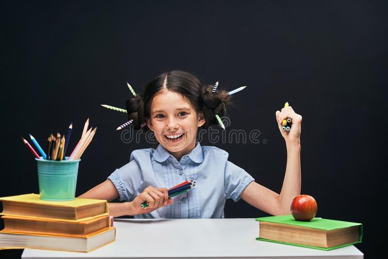 Радостная маленькая девочка сидя на таблице с карандашами и учебниками Счастливый зрачок ребенка делая домашнюю работу на таблице стоковая фотография