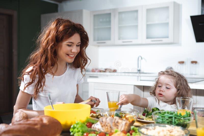 Радостная мать и дочь наслаждаясь здоровым обедающим совместно стоковое изображение rf