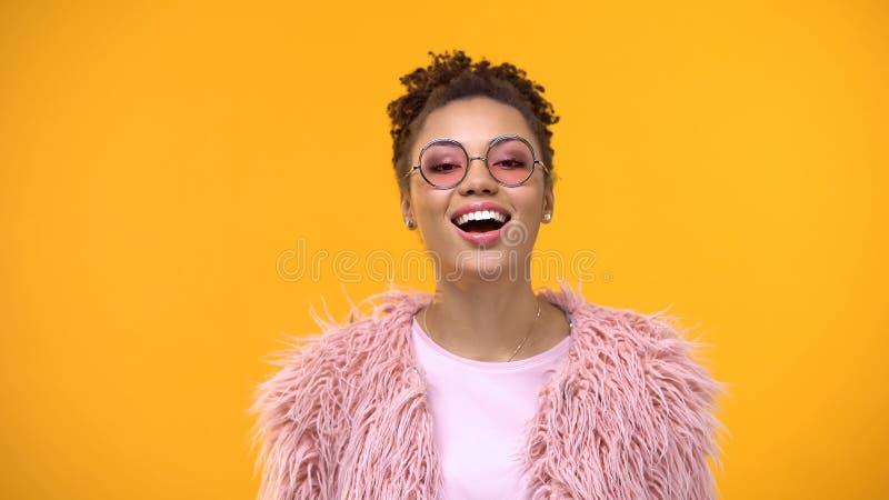 Радостная молодая женщина в модных eyeglasses и мехе на желтой предпосылке стоковые изображения rf