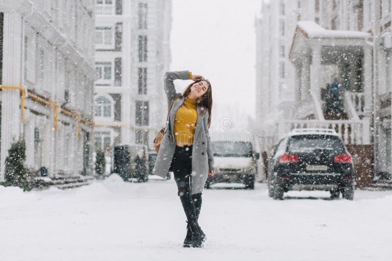 Радостная молодая женщина зимы охлаждая в снежностях на strett в большом городе Модная модель, перемещение с рюкзаком, усмехаясь стоковое изображение rf