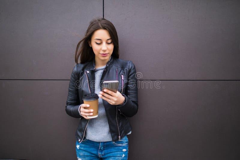 Радостная молодая женщина отправляя СМС и держа кофе пока полагающся против стены в городском снаружи стоковые фотографии rf