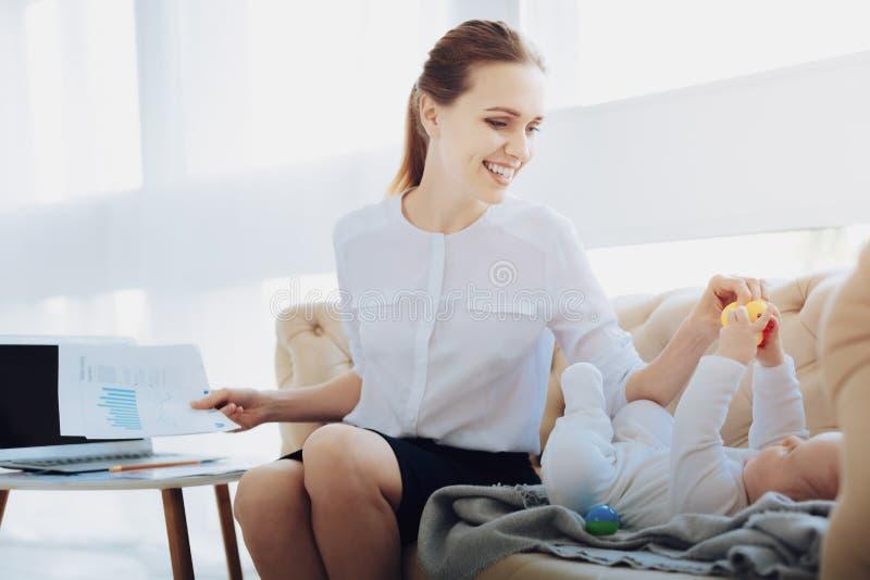 Радостная молодая мама принимая резиновую утку стоковые фото