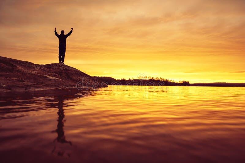 Радостная персона во время захода солнца на озере стоковое фото