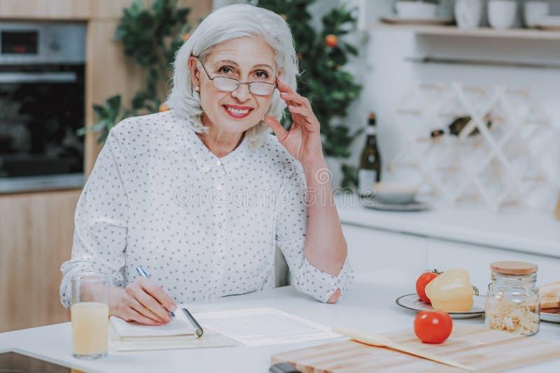 Радостная пожилая женщина пишет рецепт во время варить стоковые изображения