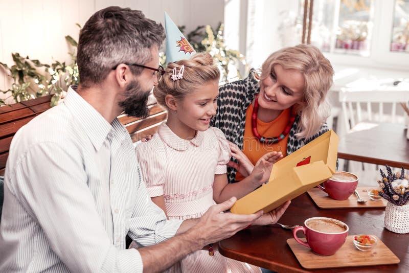 Радостная славная девушка празднуя день рождения с ее родителями стоковое фото