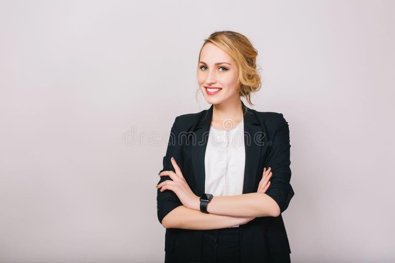 Радостная уверенная белокурая коммерсантка в костюме усмехаясь к камере изолированной на белой предпосылке Современный работник,  стоковое фото