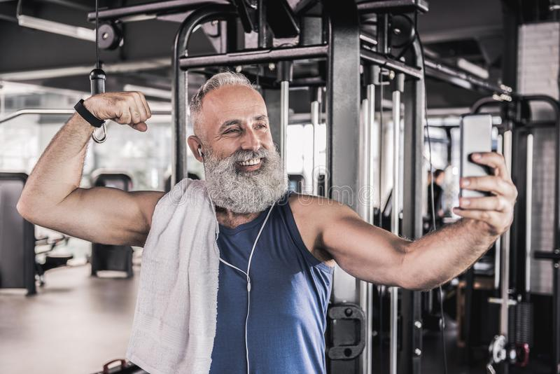 Радостное старшее мужское делая изображение себя в современном спортзале стоковое изображение rf