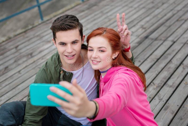 Радостные молодые пары принимая памяти помадки selfie стоковые фотографии rf