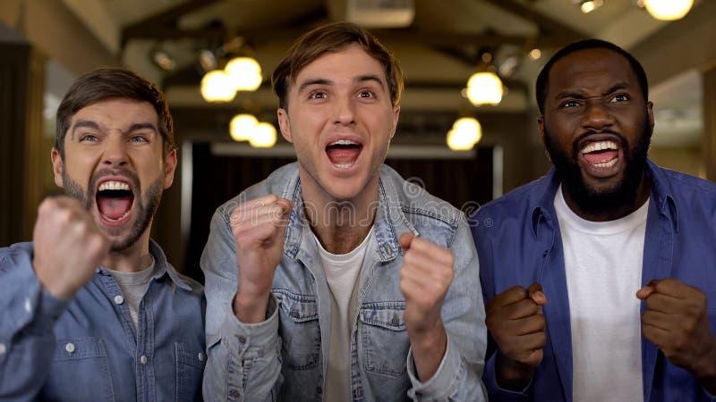 Радостные парни кричащие, укореняющ совместно для победы команды, аудитория спортивного мероприятия стоковое фото
