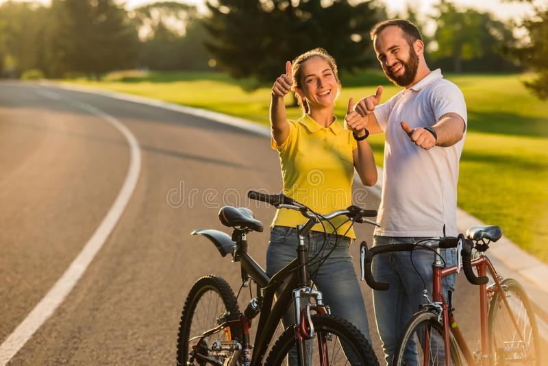 Радостные пары велосипедистов показывая жестами большие пальцы руки вверх стоковая фотография