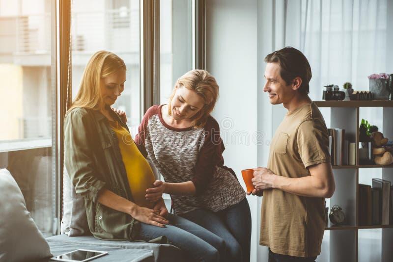 Радостные пожененные пары тратя время с суррогатной беременной женщиной стоковые изображения
