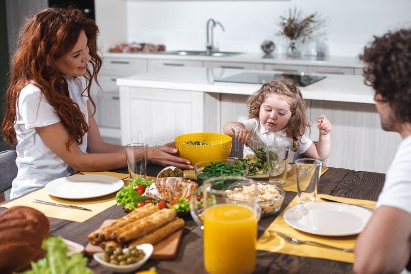 Радостные родители и девушка обедая совместно в кухне стоковое изображение