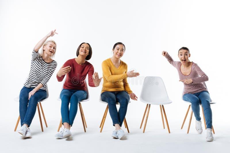 Радостные счастливые женщины приглашая вас стоковое фото