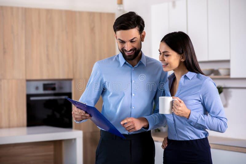 Радостные youing коллеги стоя в кухне стоковое изображение