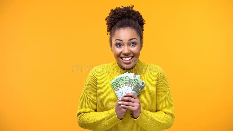 Радостный Афро-американский пук евро, высокооплачиваемая работа удерживания женщины, зарплата стоковые фото