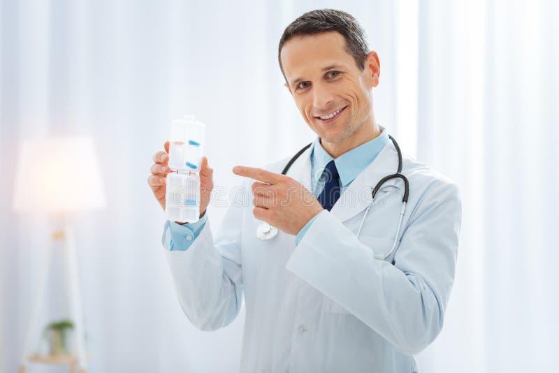 Радостный держатель рекламы медицинского работника для пилюлек стоковое фото rf