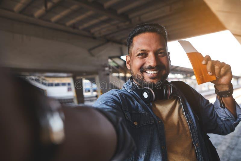 Радостный индусский человек делая selfies на железнодорожном вокзале стоковое фото