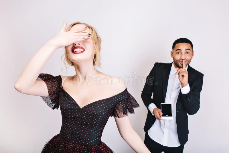 Радостный красивый парень с кольцом делая сюрприз за привлекательной возбужденной молодой женщиной с закрытыми глазами на белой п стоковое фото rf