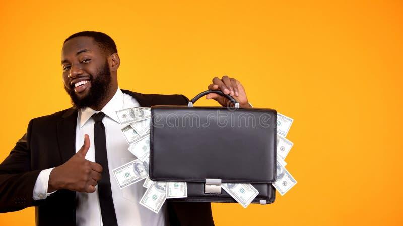 Радостный красивый чернокожий человек в сумке удерживания костюма с наличными деньгами, показывая большие пальцы руки-вверх стоковая фотография rf