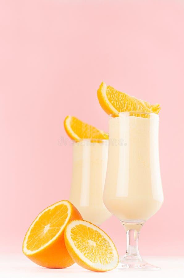 Радостный красочный десерт апельсинов молока с сочными кусками на современной элегантной розовой предпосылке цвета, вертикальной стоковое фото rf