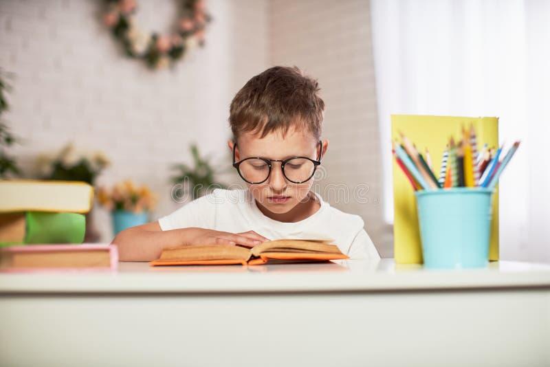 Радостный мальчик сидя на таблице с карандашами и учебниками Счастливый зрачок ребенка делая домашнюю работу на таблице стоковое изображение rf