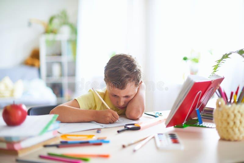 Радостный мальчик сидя на таблице с карандашами и учебниками Счастливый зрачок ребенка делая домашнюю работу на таблице неправиль стоковые фотографии rf