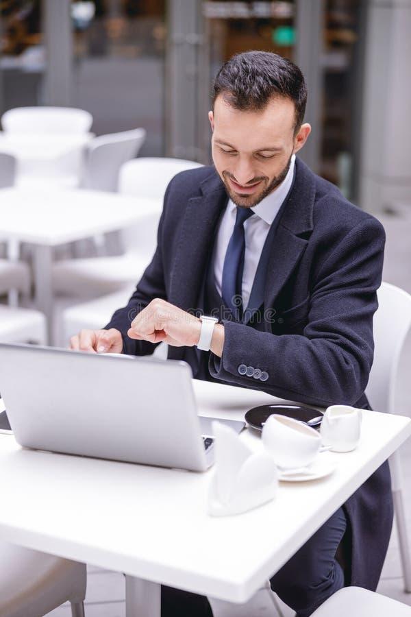 Радостный молодой человек смотрит на свои часы стоковые изображения