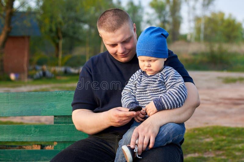 Радостный отец сидя с его раздражанным сыном на стенде в парке стоковая фотография rf