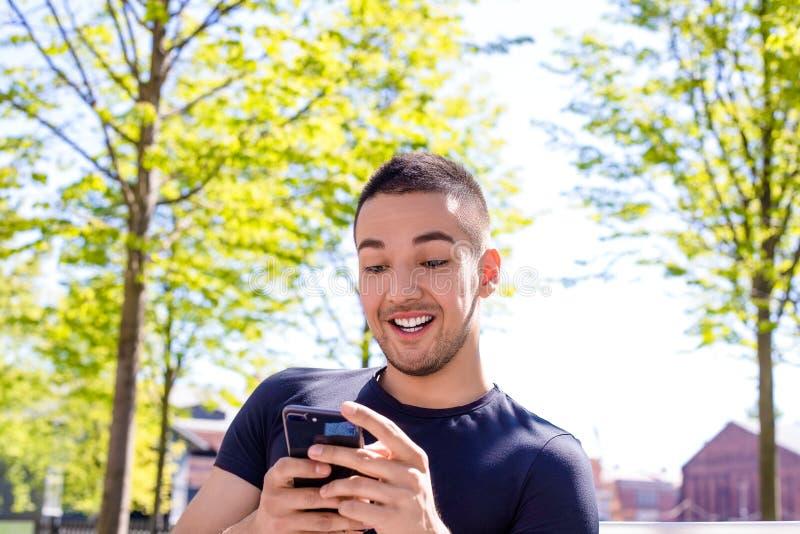 Радостный подросток играя игры на смартфоне во время остатков outdoors стоковое изображение rf