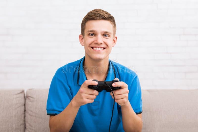 Радостный подросток играя консоль с кнюппелем в руках стоковые фотографии rf