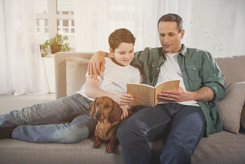 Радостный родитель и ребенок ослабляя дома с щенком таксы стоковая фотография