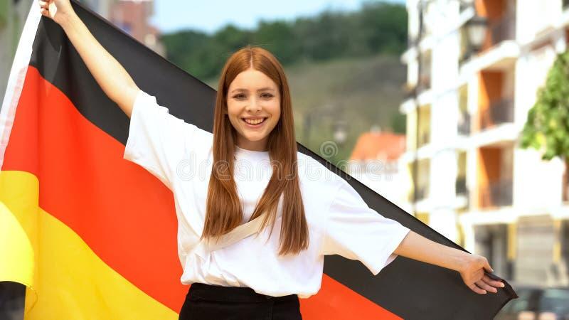 Радостный рыжий подросток, размахивая немецким флагом и улыбаясь на камеру, патриотизм стоковые изображения rf