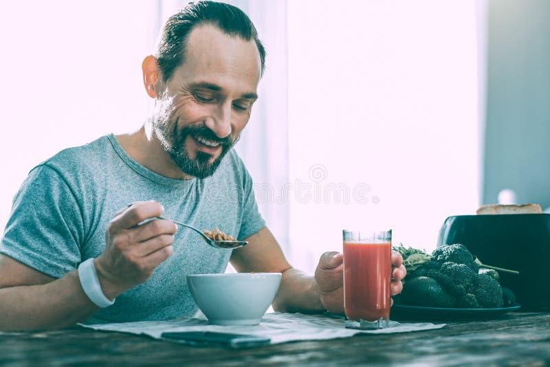 Радостный славный человек имея вкусный завтрак дома стоковая фотография rf