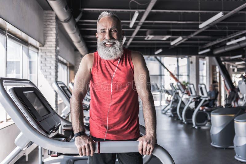 Радостный старый стильный мужчина тратит время в атлетическом центре стоковое фото