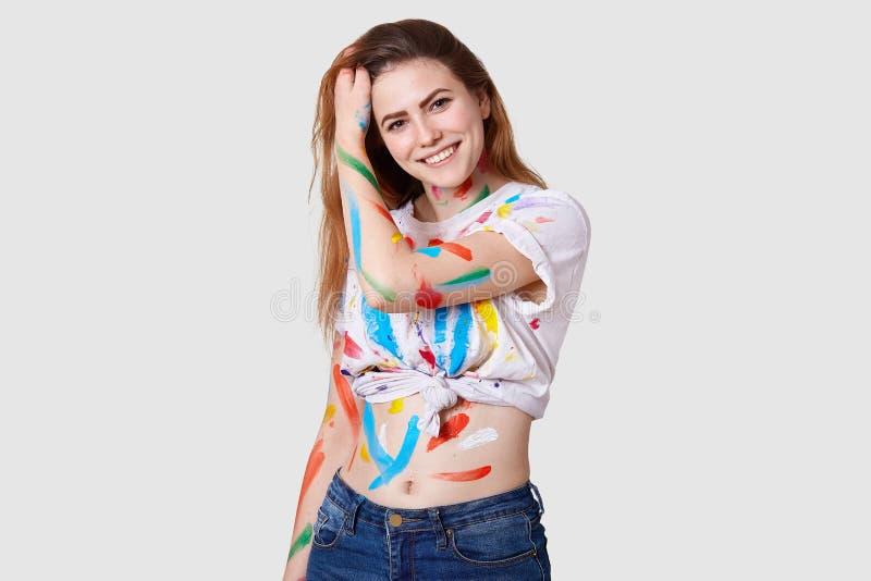 Радостный творческий женский художник одетый в белой случайной верхней части и джинсы, имеют пятна watercolours на одеждах, чувст стоковые фотографии rf
