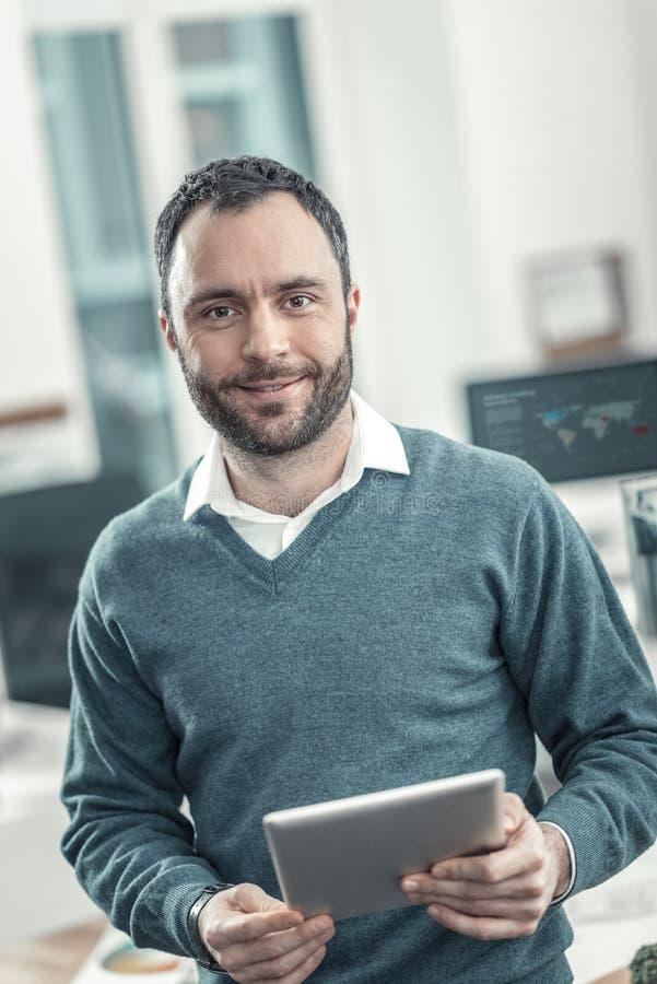 Радостный умный взрослый инженер используя планшет стоковая фотография