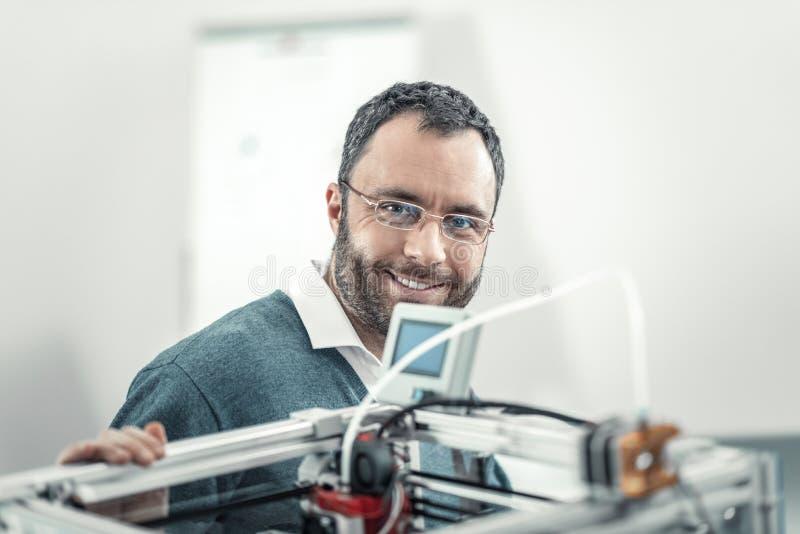 Радостный умный взрослый инженер находясь на работе стоковое фото