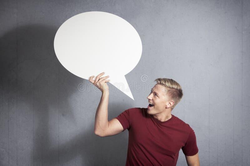 Радостный человек держа пустой воздушный шар речи. стоковое изображение