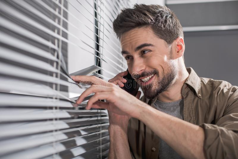 Радостный человек смотря через окно офиса стоковые фото