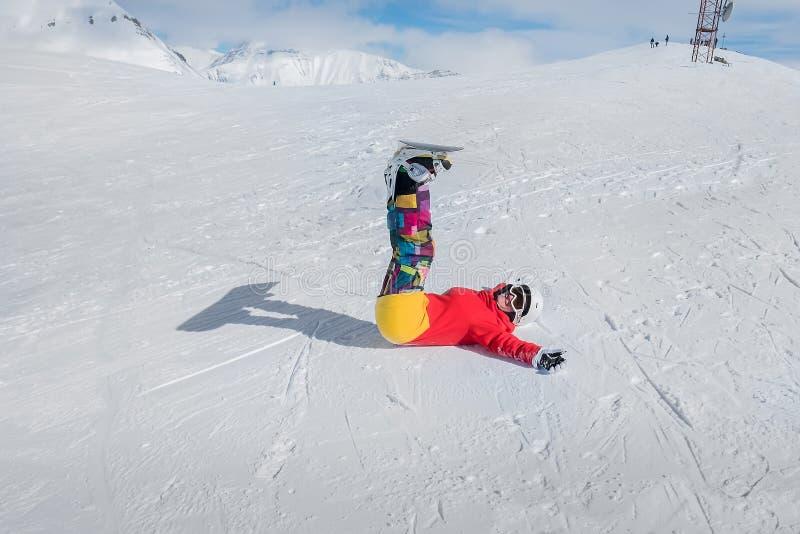 Радостный snowboarder девушки лежит на снеге при протягиванные оружия стоковое фото